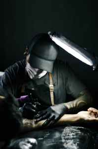 tattoo artist in black gloves drawing a tattoo on a person s arm